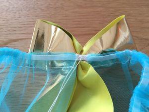 チュールスカートのゴムの前中心にリボンを配置して、糸を渡して固結びをし、糸を切ります。