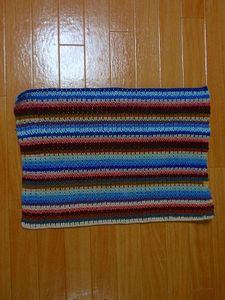 それ以降、各段ごとに好きな配色で毛糸を付け、長編み2目・鎖1目の模様で39段まで編み、糸始末をする。 縦40㎝横55㎝です。