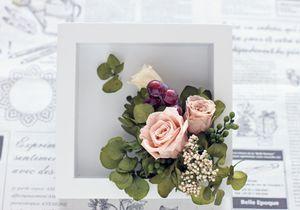 アジサイに木工ボンドをつけて花の周りにさし、バーゼリアを何箇所かにさす。1つ切り分けておいたアジサイの花の裏にグルーをつけて、フレーム底部の左上につけて、ポイントにする。