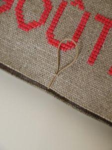 クロスステッチをした麻布の中心部に写真のような状態でコードを糸で留めます♪ ※布の上部から約8mmの位置で糸で留めるのがベスト