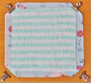斜辺がタオルの角と触れ合う位置になるところで、布の方の生地の角っこを、三角に折ります。 折った部分は、タオルの後ろ側にしておきます。