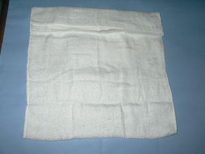 フェイスタオルを折ります。 まず半分に折ります。 端の部分を中に織り込むように折りたたんでいきます。