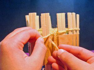 セロテープでとめた毛糸で割り箸にかかっている毛糸を下からすくいます。